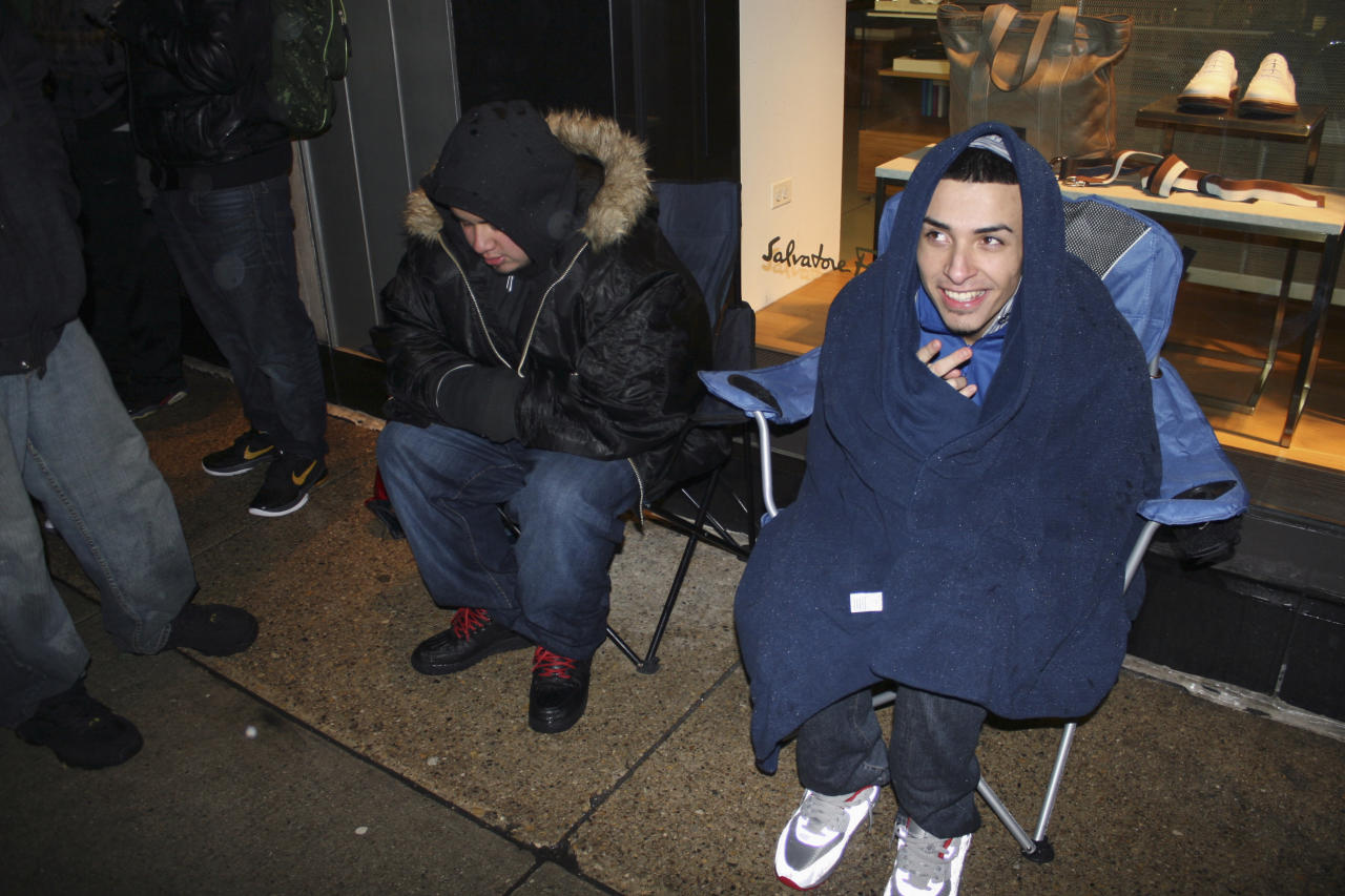 """In this photo taken Feb. 23, 2012, self-proclaimed """"sneakerheads"""" camp out overnight in freezing rain outside a downtown Chicago shoe store for a release of limited edition Nike basketball shoes. The group of about 60 people was much more orderly than crowds in other cities, including Orlando, where police were called in to control crowds that were rushing for shoes. Sneakerheads collect new and vintage shoes, many of them limited edition sports shoes that carry the names of basketball greats such as Michael Jordan and Lebron James. The craze started back in the 1980s with the release of the first Air Jordan shoe but has gotten more attention recently as sneakerheads have clamored for shoes. (AP Photo/Martha Irvine)"""