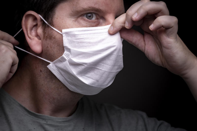 Man fits coronavirus face mask close to nose adjusts wire to stop hot air fogging on glasses