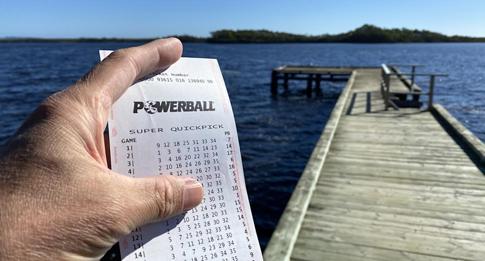 A man holding a winning Powerball ticket standing by the water