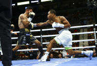 Jorge Linares, left, takes a hit from Devin Haney during the WBC lightweight title boxing match Saturday, May 29, 2021, in Las Vegas. (AP Photo/Chase Stevens)