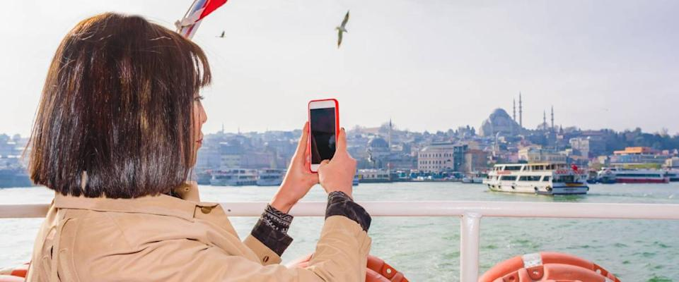 Beautiful woman takes photos while cruising in ferry with view of Suleymaniye Mosque and Eminonu Town in Istanbul,Turkey