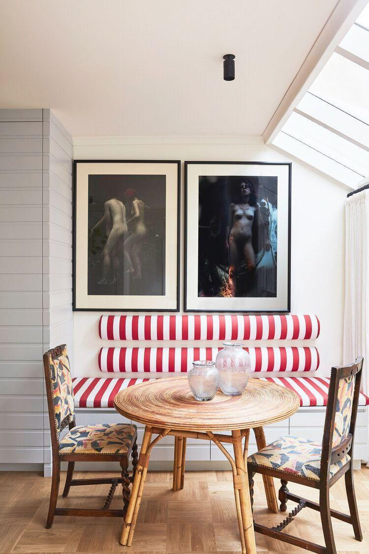 """<p>Channel the whimsy of a circus tent with fabric that features thick, bold red and white stripes. And instead of upholstering the wall behind your banquette the classic way (mimicking the back of a sofa), recreate this bolster-inspired take designed by <a href=""""https://tamsinjohnson.com/"""" rel=""""nofollow noopener"""" target=""""_blank"""" data-ylk=""""slk:Tamsin Johnson"""" class=""""link rapid-noclick-resp"""">Tamsin Johnson</a>. Paired with moody and provocative framed photographs, casual rattan table, and modern dove gray walls, the playful banquette takes on a unique and versatile persona. </p>"""