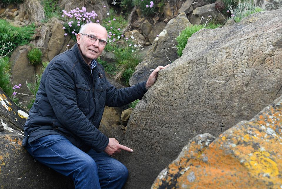 French local councillor in charge of small heritage Michel Paugam poses on May 7, 2019 as he shows inscriptions composing indecipherable words on a rock in the Brittany village of Plougastel-Daoulas. (Photo by FRED TANNEAU/AFP/Getty Images)