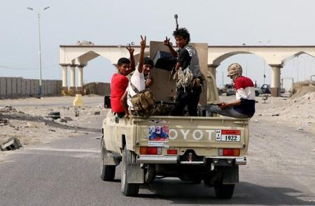 Southern separatist fighters patrol a road during clashes with government forces in Aden