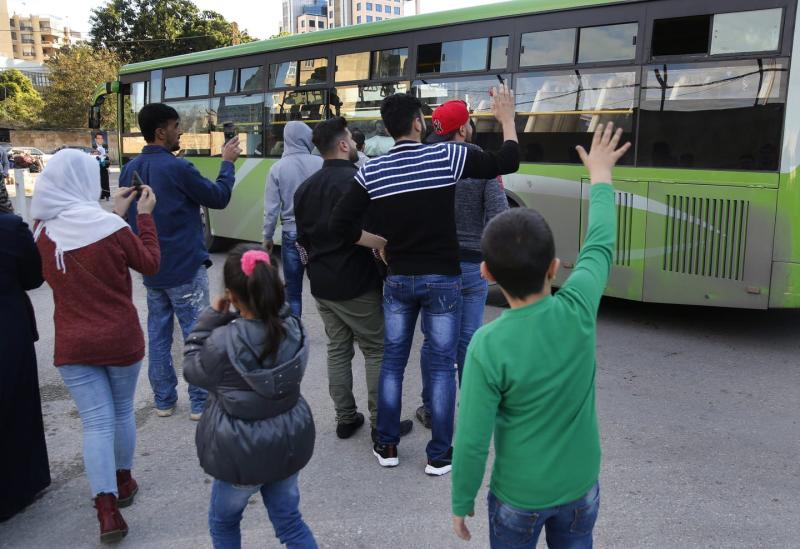 People stand near a green bus waving to its occupants.