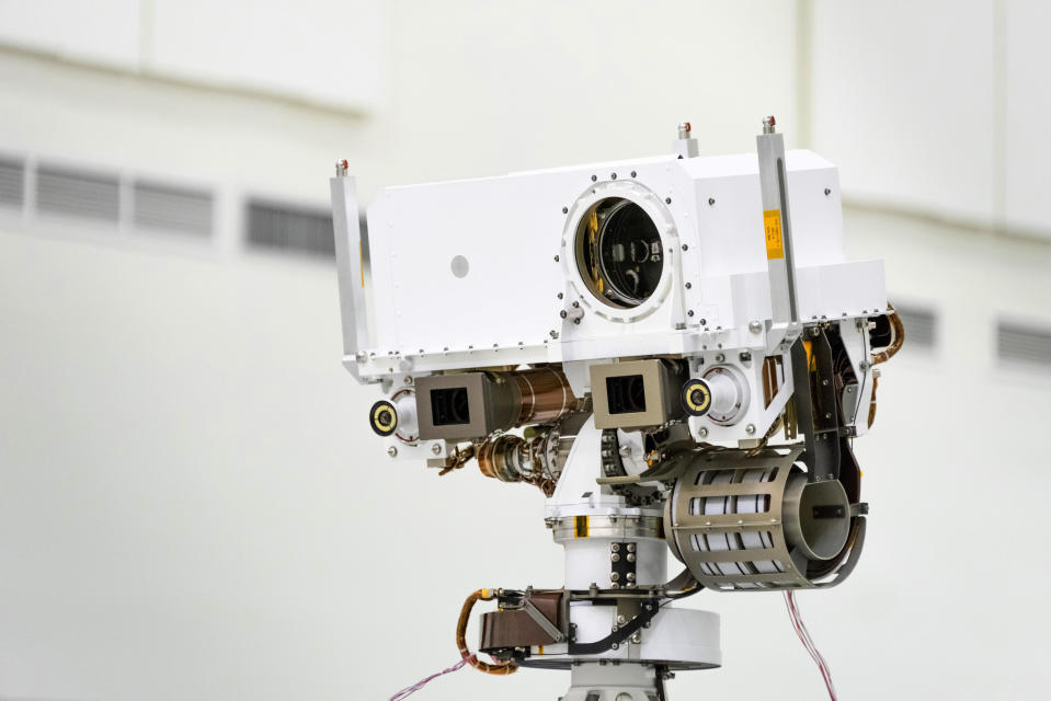 This July 23, 2019 photo made available by NASA shows the head of the Mars rover Perseverance's remote sensing mast which contains the SuperCam instrument in the large circular opening, two Mastcam-Z imagers in gray boxes, and next to those, the rover's two navigation cameras, at the Jet Propulsion Laboratory in Pasadena, Calif. The robotic vehicle will hunt for rocks containing biological signatures, if they exist. (NASA/JPL-Caltech via AP)