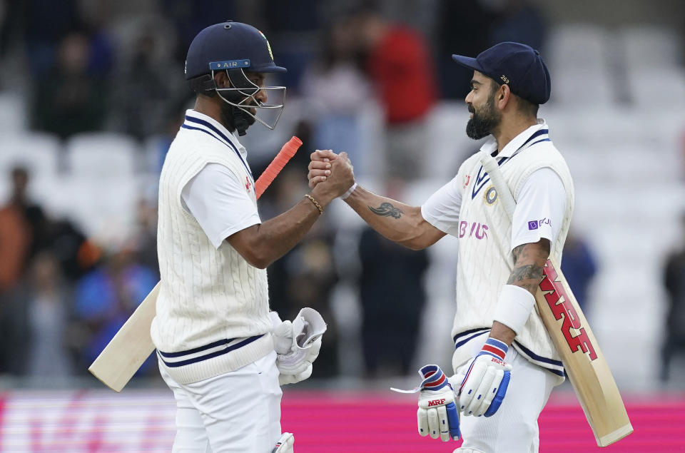 India's captain Virat Kohli, right, and batting partner Cheteshwar Pujara celebrate at the end of play on the third day of third test cricket match between England and India, at Headingley cricket ground in Leeds, England, Friday, Aug. 27, 2021. (AP Photo/Jon Super)