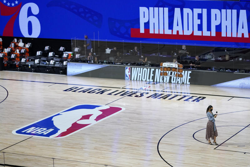 "Malika Andrews in the bottom right corner on the NBA court that says ""Black Lives Matter."""