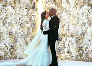 """<p>Kim Kardashian and Kanye West <a href=""""https://www.popsugar.com/celebrity/Kim-Kardashian-Kanye-West-Wedding-Facts-43470534"""" rel=""""nofollow noopener"""" target=""""_blank"""" data-ylk=""""slk:married"""" class=""""link rapid-noclick-resp"""">married</a> in a 16th-century-era fortress in Florence, Italy, in May 2014. They exchanged vows in front of a flower wall as a backdrop, and there were also no E! cameras at the ceremony. </p>"""