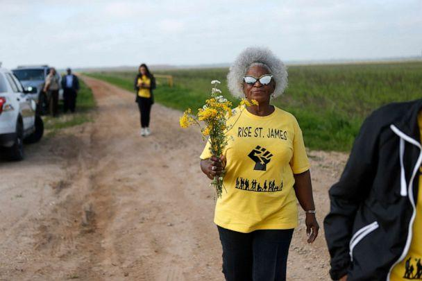 PHOTO: Gail LeBoeuf, a member of RISE St. James, carries flowers as they seek access to a burial site on property owned by Formosa in St. James Parish, La., March 11, 2020. (Gerald Herbert/AP)