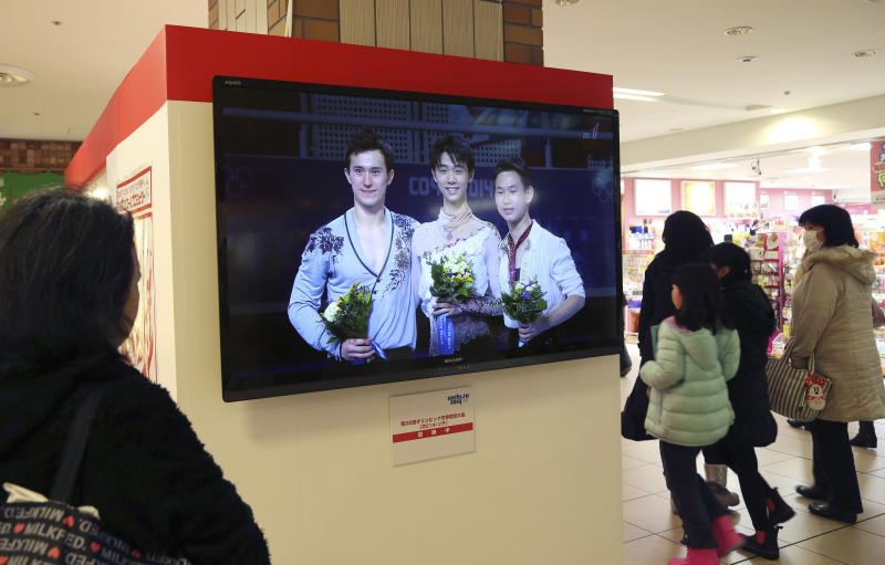 A woman watches a public TV showing recordings of men's figure Skating Singles medalists, gold medalist Yuzuru Hanyu of Japan, center, silver medalist Patrick Chan of Canada, left, and bronze medalist Denis Ten of Kazakhstanat, at a special Sochi olympic booth at Tokyo Station in Tokyo, Saturday, Feb. 15, 2014. Japan celebrated Hanyu's historic win in men's figure skating at the break of dawn Saturday, rejoicing in the country's first-ever gold medal in the Olympic event. (AP Photo/Koji Sasahara)