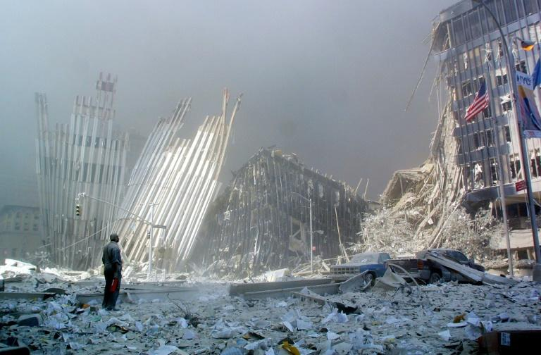 In a photo taken on September 11, 2001, a man stands in the rubble, and calls out asking if anyone needs help, after the collapse of the first World Trade Center Tower in New York