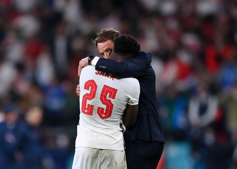 LONDON, ENGLAND - JULY 11: Bukayo Saka of England is consoled by Head Coach, Gareth Southgate after his penalty miss during the UEFA Euro 2020 Championship Final between Italy and England at Wembley Stadium on July 11, 2021 in London, England. (Photo by Laurence Griffiths/Getty Images)