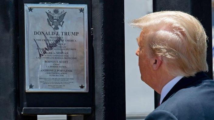 President Trump inspects a section of wall with a signed plaque on it