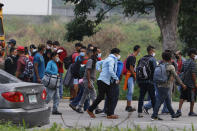 Migrants trying to reach the U.S. border walk along a highway in Choloma, Honduras, Thursday, Jan. 14, 2021. About 200 Honduran migrants resumed walking toward the border with Guatemala early Thursday, a day before a migrant caravan was scheduled to depart San Pedro Sula. (AP Photo/Delmer Martinez)