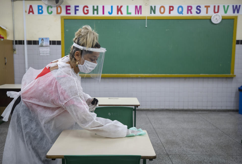 Marilene de Oliveira Paixao disinfects a student desk at the EMEF Sylvia Martin Pires public school in Sao Paulo, Brazil, Monday, March 8, 2021. Paixao, the mother of a student at the school, was hired for a temporary job as part of a program by the city's education secretary to help mothers who lost their jobs during the pandemic. (AP Photo/Andre Penner)