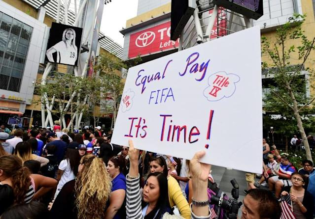 A US women's soccer fan displays a sign calling for equal pay at a rally to celebrate last year's US title run at the Women's World Cup (AFP Photo/ROBYN BECK)