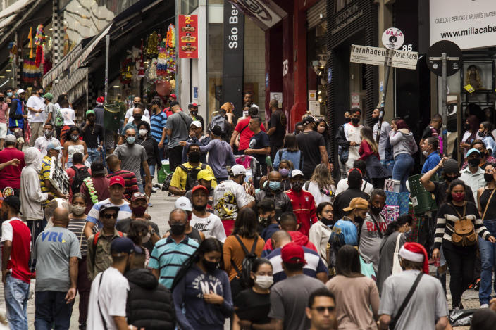 """People shop along the street """"25 de Marco,"""" an outdoor market area, days before a COVID-19 lockdown goes into effect in Sao Paulo, Brazil, Wednesday, Dec. 23, 2020. Only essential business will be allowed to operate from Dec. 25 - 27 and Jan. 1 - 3. (AP Photo/Carla Carniel)"""