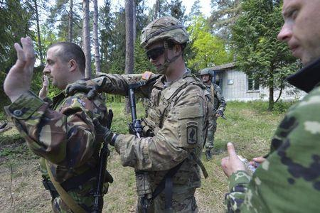 """A serviceman of the U.S. Army's 173rd Airborne Brigade Combat Team (C) trains Ukrainian soldiers during a joint military exercise called """"Fearless Guardian 2015"""" at the military training area in Yavoriv, outside Lviv, Ukraine, May 12, 2015. REUTERS/Oleksandr Klymenko"""
