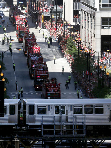 The 2013 Stanley Cup Champion Chicago Blackhawks ride in a victory parade down Washington Street as an elevated train passes by Friday, June 28, 2013 in Chicago. The Blackhawks celebrate the team's second championship in four years. (AP Photo/Charles Rex Arbogast)