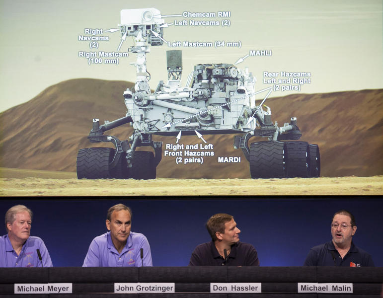 Scientists comment on the seven cameras aboard the Curiosity Mars Rover, background, during a media briefing of the Mars Science Laboratory, science overview news briefing at NASA's Jet Propulsion Laboratory, in Pasadena, Calif., Thursday, Aug. 2, 2012. From left: Michael Meyer, scientist, Mars Exploration Program lead, John Grotzinger, MSL project scientist, California Institute of Technology, Don Hassler, principal investigator, Radiation Assessment Detector on MSL, Michael Malin, principal investigator, Mars Descent Imager on MSL. Curiosity is scheduled to land on Mars Sunday night. (AP Photo/Damian Dovarganes)