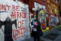 FILE PHOTO: A man wearing a protective face mask as he walks by murals as the spread of coronavirus disease (COVID-19) continues along Houston Street in New York City