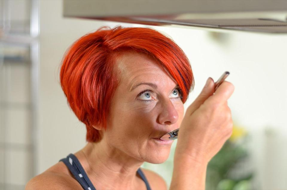 Close up Adult Redhead Woman in Sleeveless Shirt, Tasting her Recipe using a Spoon