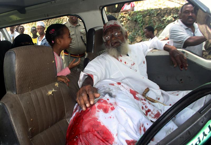 The daughter of Aboud Rogo, a Muslim cleric facing terror-related charges, cries out as Rogo's father holds the slumped and blood stained body of his son in the vehicle where Aboud Rogo was shot dead near the Jomo Kenyatta Public beach, Mombasa Kenya, Monday, Aug. 27, 2012. Gunmen in Kenya's coastal city of Mombasa shot dead a Muslim cleric accused by Washington and the United Nations of supporting al-Qaida-linked militants in Somalia, sparking rioting by youths who burned at least one police car and stoned businesses. Human rights groups say the killing on Monday of Aboud Rogo falls into a pattern of extrajudicial killings and forced disappearances of suspected terrorists, allegedly being orchestrated by Kenyan police. (AP Photo)