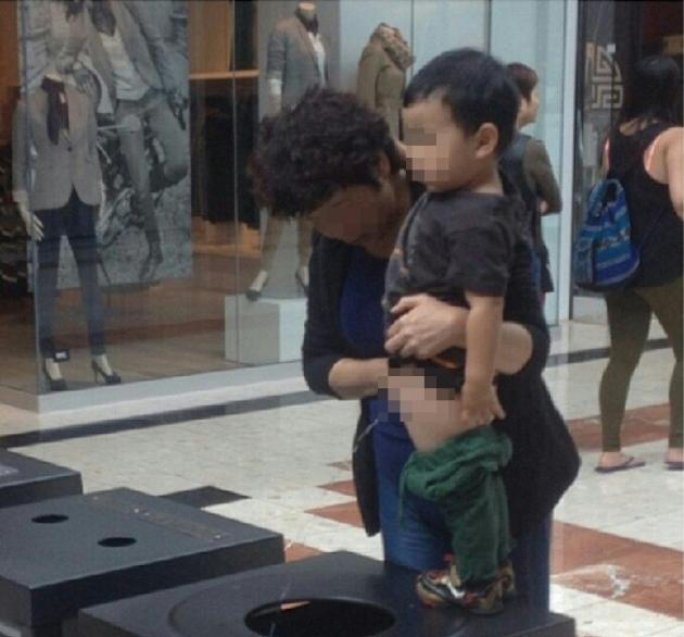 A boy urinates in a bin in an upscale Canadian shopping mall. (Photo courtesy of Brandon Beavis's Twitter)