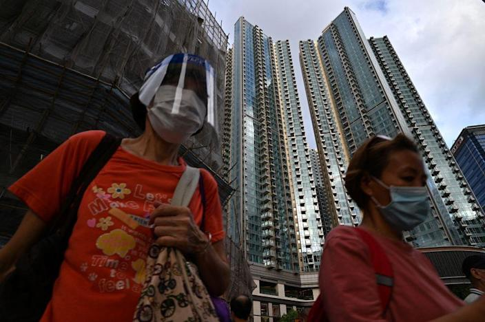 """Pedestrians walk past the Grand Central (R) residential building complex in Hong Kong on May 28, 2021, where a 1.4 million USD (10.8 million HKD) one-bedroom apartment has been offered for a lucky draw's grand prize for which all Hong Kong residents aged 18 and above who have received both doses of the COVID-19 vaccines will be eligible to register.<span class=""""copyright"""">Anthony Wallace—AFP/Getty Images</span>"""