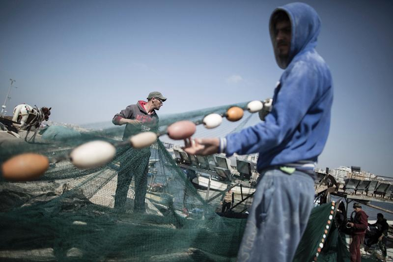 Palestinian fishermen load their nets onto a boat before sailing into the waters of the Mediterranean Sea in Gaza City on May 3, 2017 after Israel eased restrictions on Gaza fishermen (AFP Photo/Mahmud Hams)