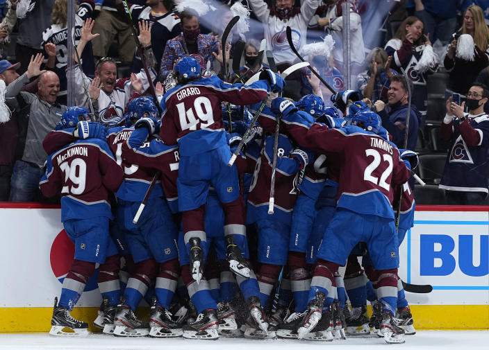 Colorado Avalanche players congratulate Mikko Rantanen after his overtime goal against the Vegas Golden Knights during Game 2 of an NHL hockey Stanley Cup second-round playoff series Wednesday, June 2, 2021, in Denver. (AP Photo/Jack Dempsey)