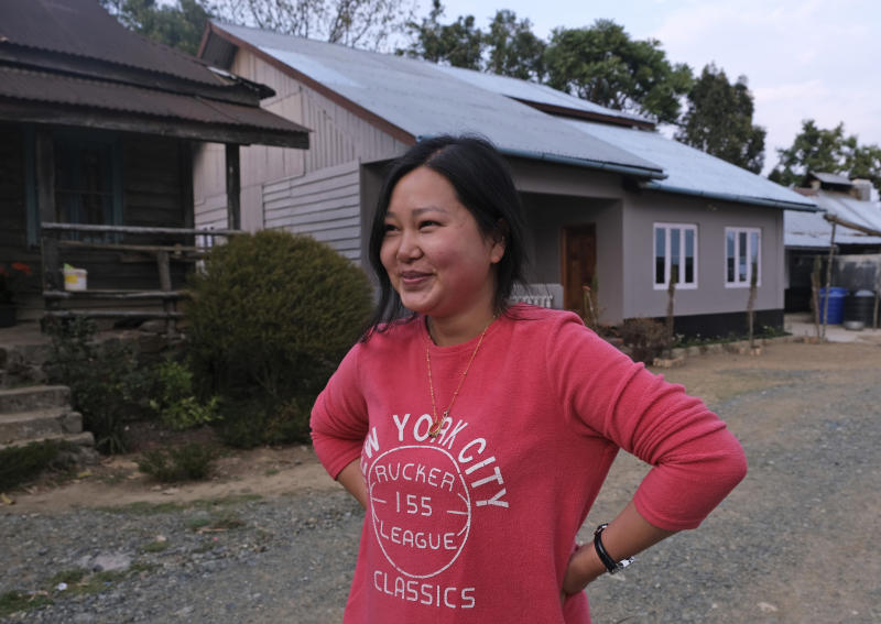 """In this Sunday, March 22, 2020, photo, Ringhuila Zimik, 26, smiles as she speaks about the rumor of medicine being sprayed from the sky to contain a new virus, in Shangshak village, in the northeastern Indian state of Manipur. """"We all heard about it. I didn't know whether to believe it or not but stayed indoors anyway,"""" she said. As India and other South Asian nations brace for the likely spread of the virus, they are facing another battle: reams of misinformation, misleading rumors and false claims. This battle has been hard to contain as social media continues to be rife with bogus remedies to tales of magic cure and potentially dangerous medical advice. (AP Photo/Yirmiyan Arthur)"""