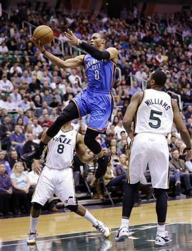 Oklahoma City Thunder's Russell Westbrook (0) goes to the basket as Utah Jazz's Randy Foye (8) and Mo Williams (5) watch in the first quarter during an NBA basketball game, Tuesday, April 9, 2013, in Salt Lake City. (AP Photo/Rick Bowmer)