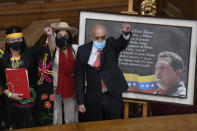 Jorge Rodriguez, right, lifts his fist after being sworn-in as president of the National Assembly, in front of a photo of late President Hugo Chavez, at Congress in Caracas, Venezuela, Tuesday, Jan. 5, 2021. The ruling socialist party assumed the leadership of Venezuela's congress, the last institution in the country it didn't already control. (AP Photo/Matias Delacroix)