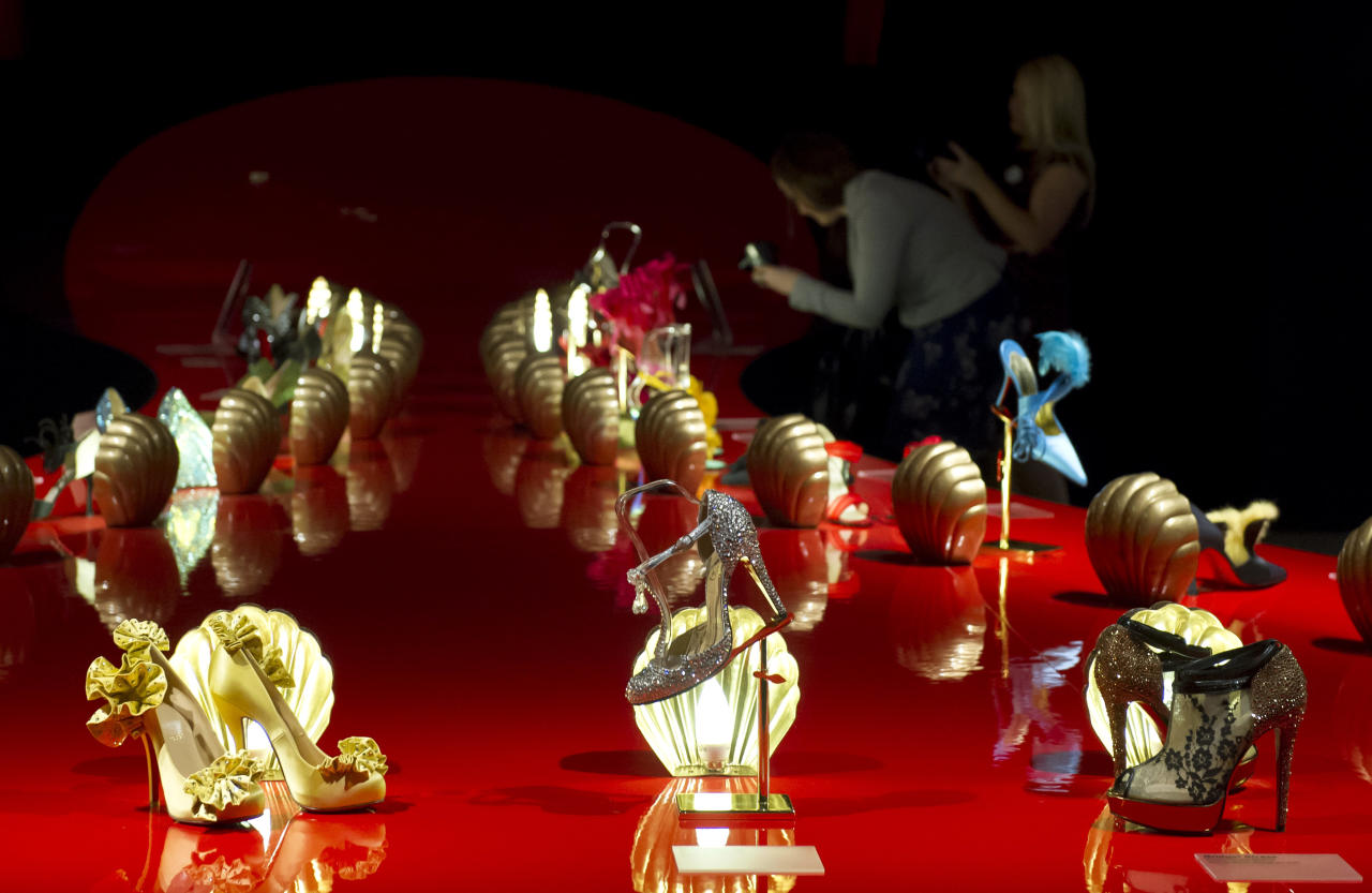 Members of the public photograph part of the first ever retrospective exhibition by French shoe designer, Christian Louboutin, at the Design Museum, London, Monday, April 30, 2012. The exhibition will be the first comprehensive presentation of Louboutin's work, and will showcase how he has helped transform the design of the shoe over the past 20 years. (AP Photo/Jonathan Short)