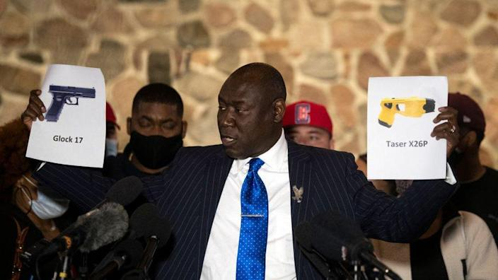 Attorney Ben Crump holds up pictures of gun and a taser during a press conference with the family of Daunte Wright