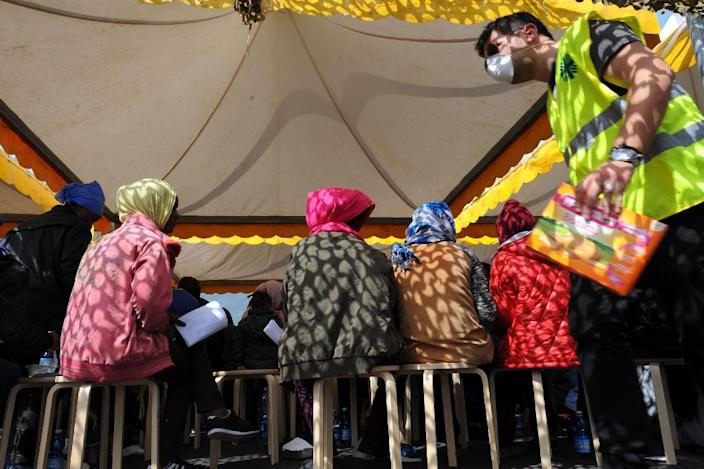 """Migrants wait under a tent after disembarking from military ship """"Bettica"""" following a rescue operation at sea on May 5, 2015 in the port of Salerno (AFP Photo/Mario Laporta)"""