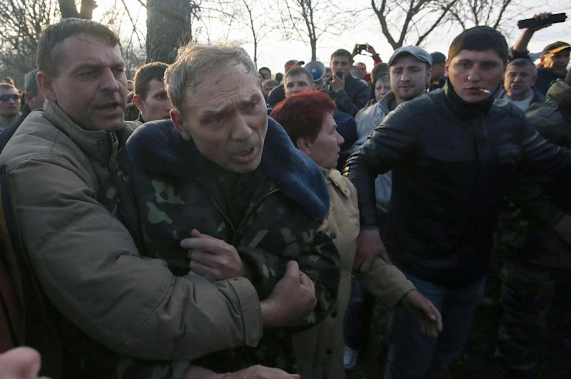 Pro-Russian activists attack Ukraine's security services anti-terrorist unit chief, Gen. Vasyl Krutov, center, after he spoke outside Kramatorsk airport, eastern Ukraine, Tuesday, April 15, 2014. In the first Ukrainian military action against a pro-Russian uprising in the east, government forces clashed Tuesday with about 30 armed gunmen at a small airport in Kramatorsk. (AP Photo/Sergei Grits)