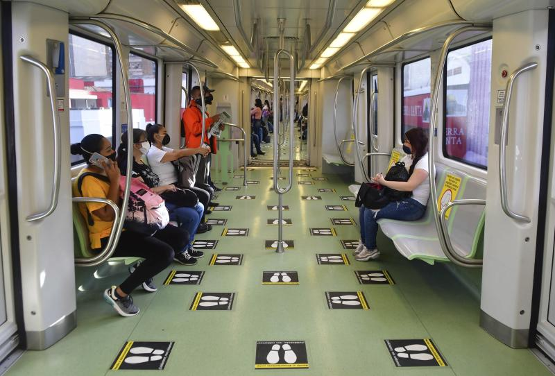 In this June 8, 2020 photo, commuters travel on a train marked with social distancing graphic cues, amid the new coronavirus pandemic, in Medellin, Colombia. The metropolis recently went five weeks without a single COVID-19 death. (AP Photo/Luis Benavides)