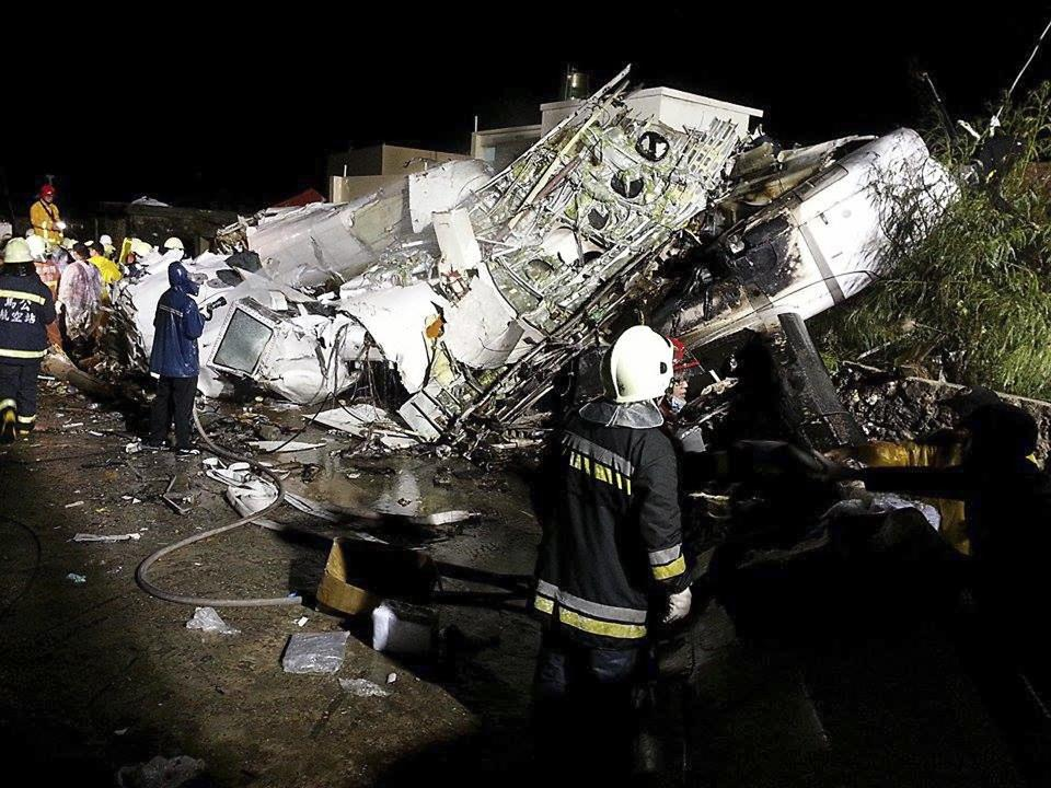 Rescue personnel survey the wreckage of TransAsia Airways flight GE222 on Taiwan's offshore island of Penghu, July 23, 2014. A TransAsia Airways turboprop ATR-72 plane crashed on its second attempt at landing during a thunderstorm on Penghu, an island off Taiwan on Wednesday, killing 47 people and setting buildings on fire, officials said. REUTERS/Wong Yao-wen (TAIWAN - Tags: ENVIRONMENT TRANSPORT DISASTER TPX IMAGES OF THE DAY)