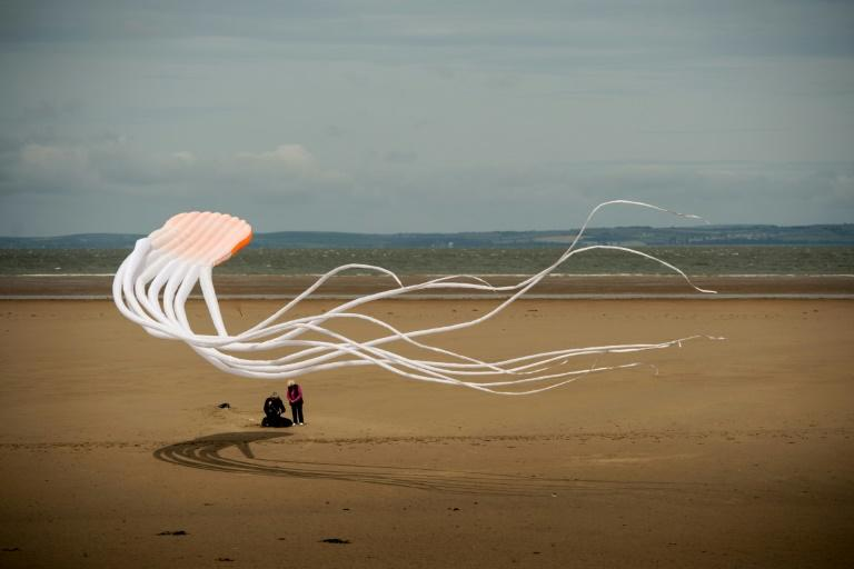 A couple fly a kite during the 'Catch The Wind Kite Festival' on the seafront in Morecambe, northern England (AFP Photo/OLI SCARFF)