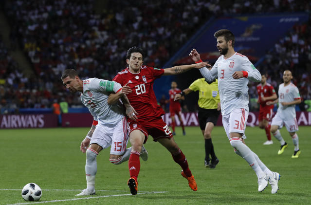 Spain's Sergio Ramos, left, fights for the ball with Iran's Sardar Azmoun, during the group B match between Iran and Spain at the 2018 soccer World Cup in the Kazan Arena in Kazan, Russia, Wednesday, June 20, 2018. (AP Photo/Manu Fernandez)
