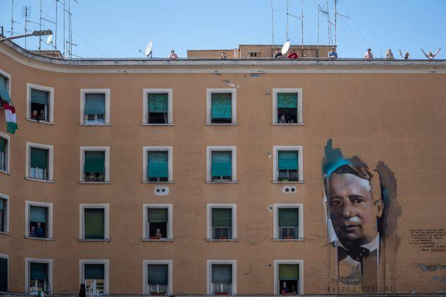 ROME, ITALY - APRIL 25: People stand at their windows and balconies to take part in a 'Liberation Day' flashmob and sing the Italian partizan song