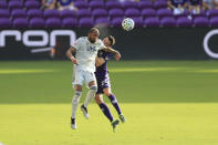 New England Revolution forward Teal Bunbury, left, and Orlando City defender Kyle Smith (24) jump to head the ball during the first half of an MLS playoff soccer match, Sunday, Nov. 29, 2020, in Orlando, Fla. (AP Photo/Matt Stamey)