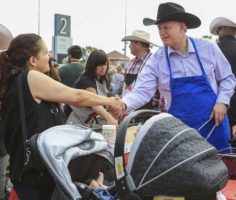Canada's Prime Minister Stephen Harper shakes hands with a woman while serving pancakes during the Calgary Stampede in Calgary