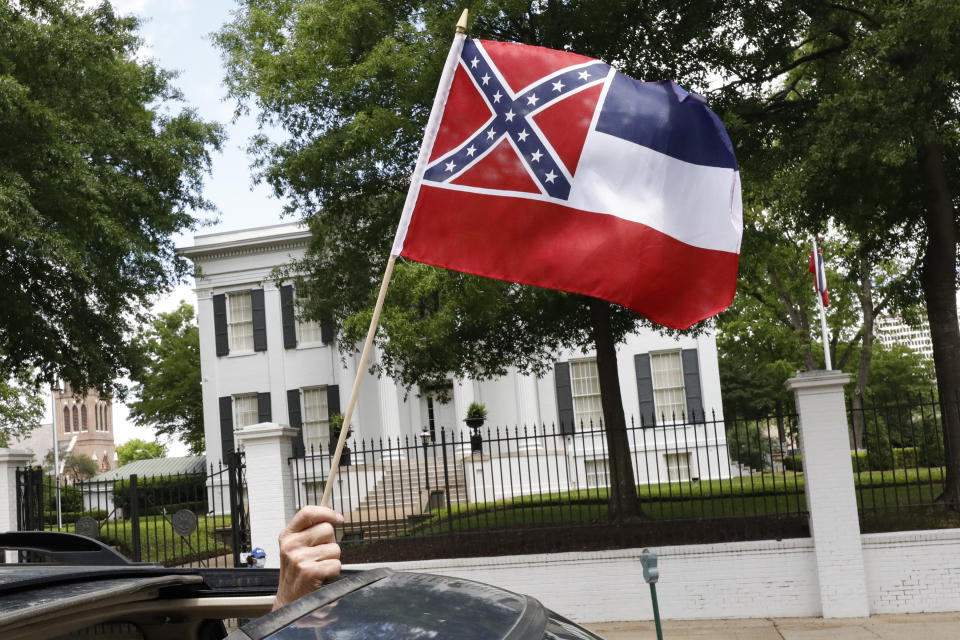 "In this April 25, 2020 photograph, a small Mississippi state flag is held by a participant during a drive-by ""re-open Mississippi"" protest past the Governor's Mansion, in the background, in Jackson, Miss. This current flag has in the canton portion of the banner the design of the Civil War-era Confederate battle flag, that has been the center of a long-simmering debate about its removal or replacement. (AP Photo/Rogelio V. Solis)"