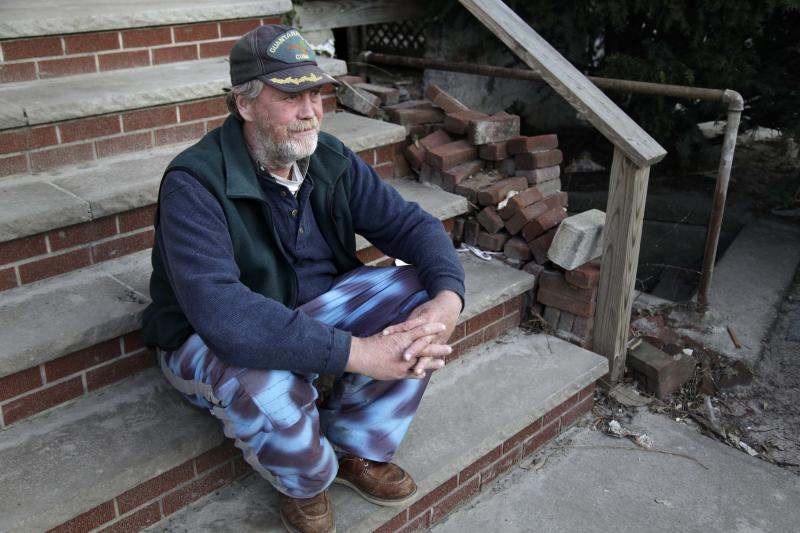 John Frawley sits on the porch of his house, which was damaged during Superstorm Sandy, on the Rockaway Peninsula in New York, Thursday, Nov. 29, 2012. Uncounted numbers of families have returned to coastal homes that are contaminated with mold, which can aggravate allergies and leave people perpetually wheezing. Others have been sleeping in houses filled with construction dust, as workers have ripped out walls and flooring. That dust can sometimes trigger asthma. (AP Photo/Seth Wenig)