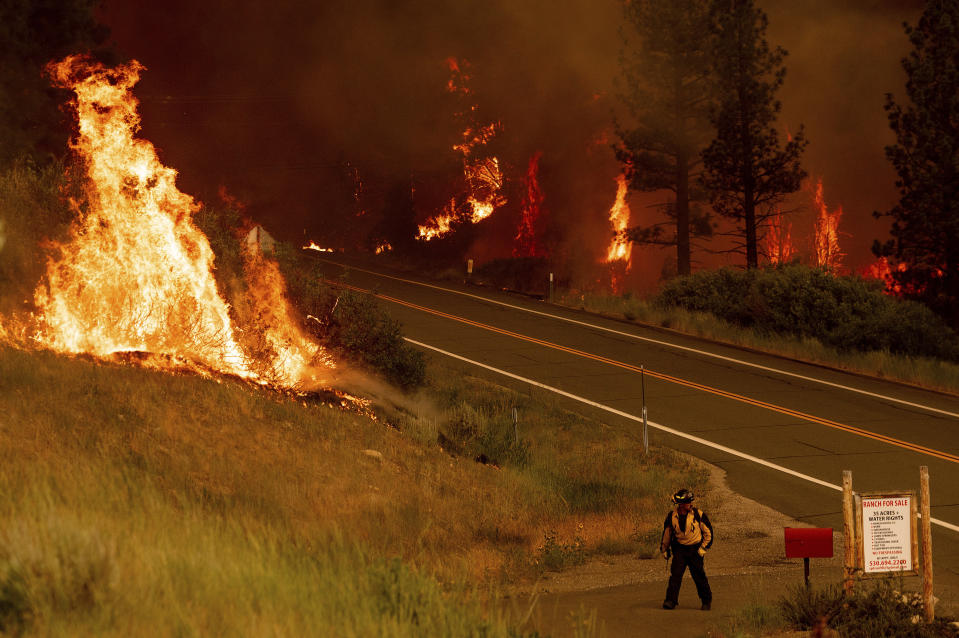 A firefighter walks towards a home while battling the Tamarack Fire in the Markleeville community of Alpine County, Calif., on Saturday, July 17, 2021. (AP Photo/Noah Berger)