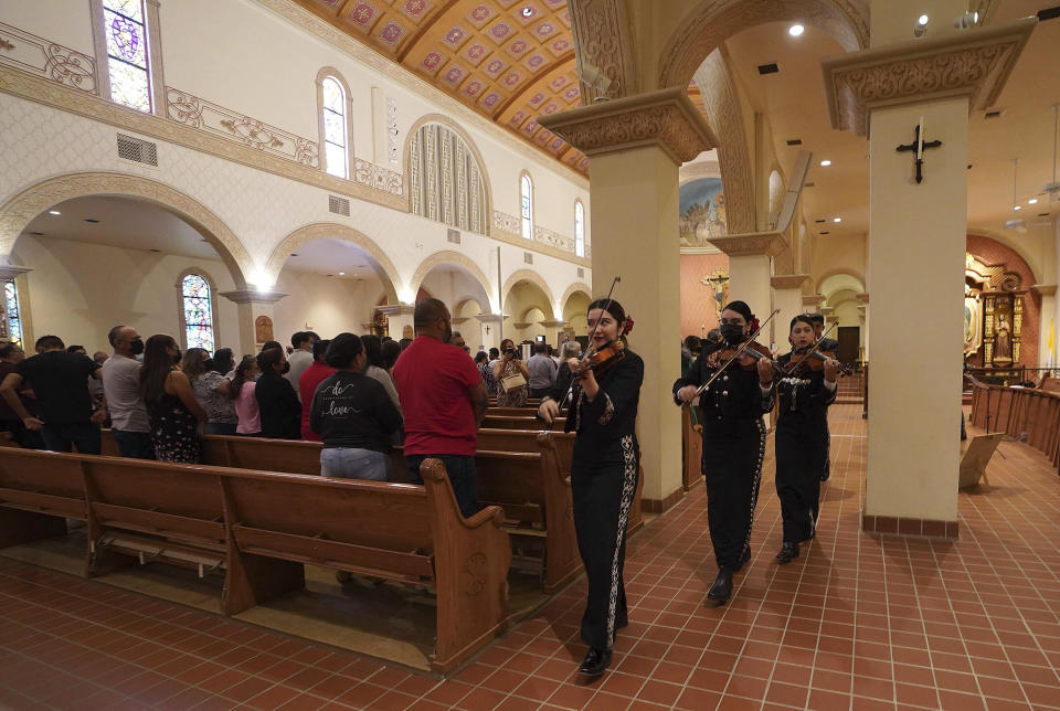 """Mariachi band Los Changuitos Feos (Ugly Little Monkeys) preform for parishioners during a morning Mass at St. Augustine Cathedral Sunday, Aug. 18, 2021 in downtown Tucson. In 1960s United States, the Chicano civil rights movement was blossoming, and mariachi musicians morphed from folksy troubadours to cultural heroes, """"symbols of Mexican identity heightened here because of multiculturalism,"""" according to Dan Sheehy, director and curator of the Smithsonian Folkways Recordings. (AP Photo/Darryl Webb)"""
